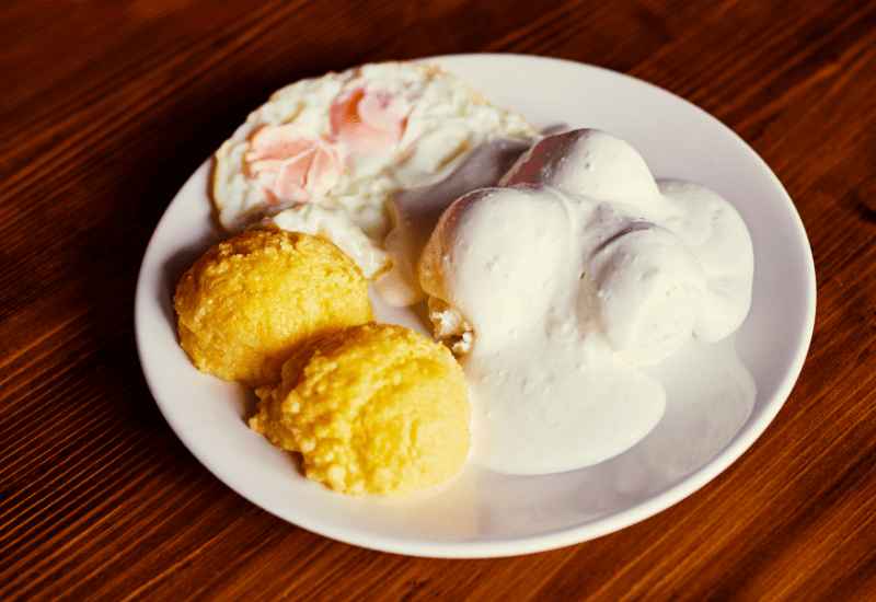 Traditional Romanian Dishes MĂMĂLIGĂ CU BRÂNZĂ ȘI CU SMÂNTÂNĂ ( Polenta With Cheese And Cream)